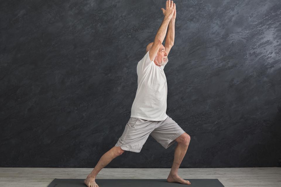 Senior man practicing yoga indoors