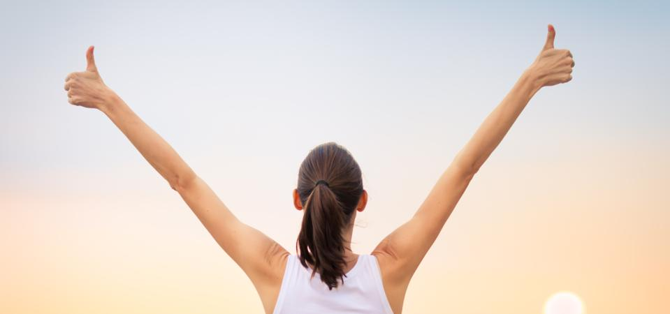 Woman with arms and thumbs up, signaling success and achievement.