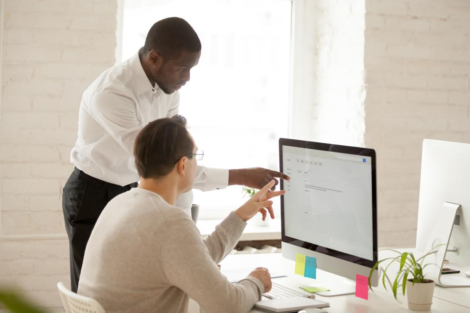African mentor helping colleague with computer work explaining application usage