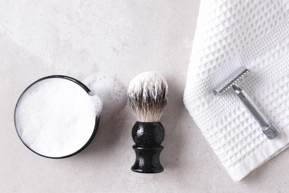 Safety razor on a towel with brush and soap on a gray tile surface