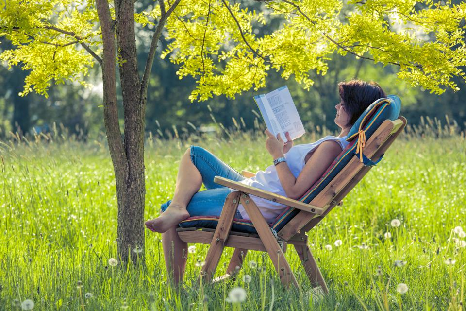 Young woman lying on deck chair in shadow under tree reading book
