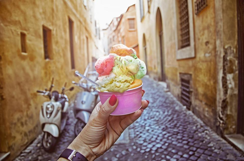 Italian ice - cream cone held in hand on the background of on vintage street atmosphere