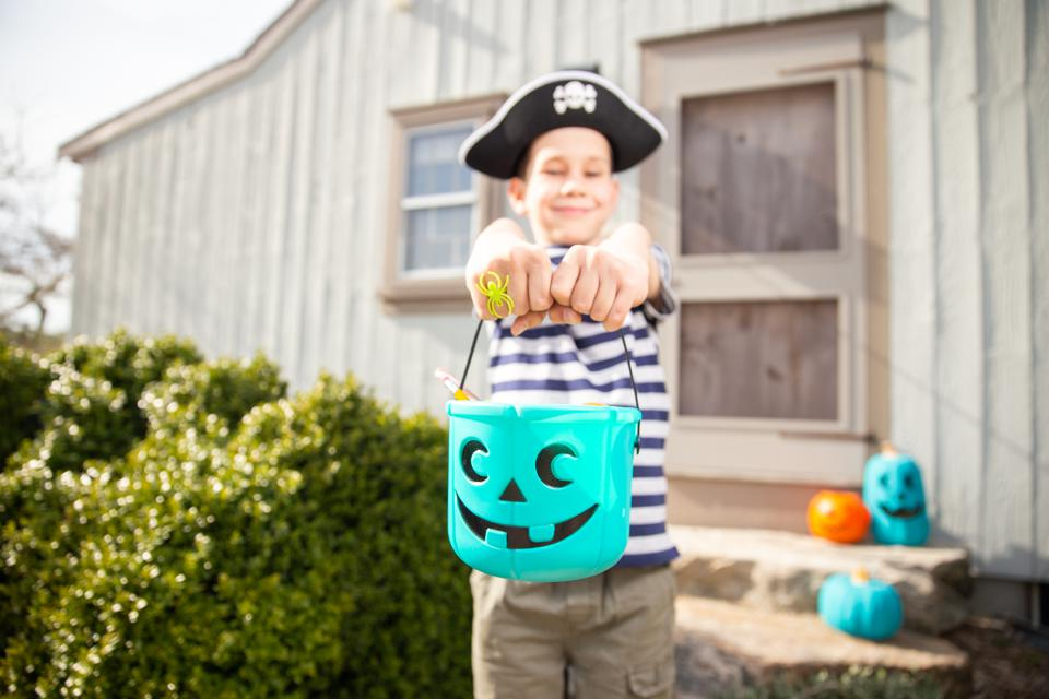 cheerful boy holding a teal bucket with toys and pencils in Halloween