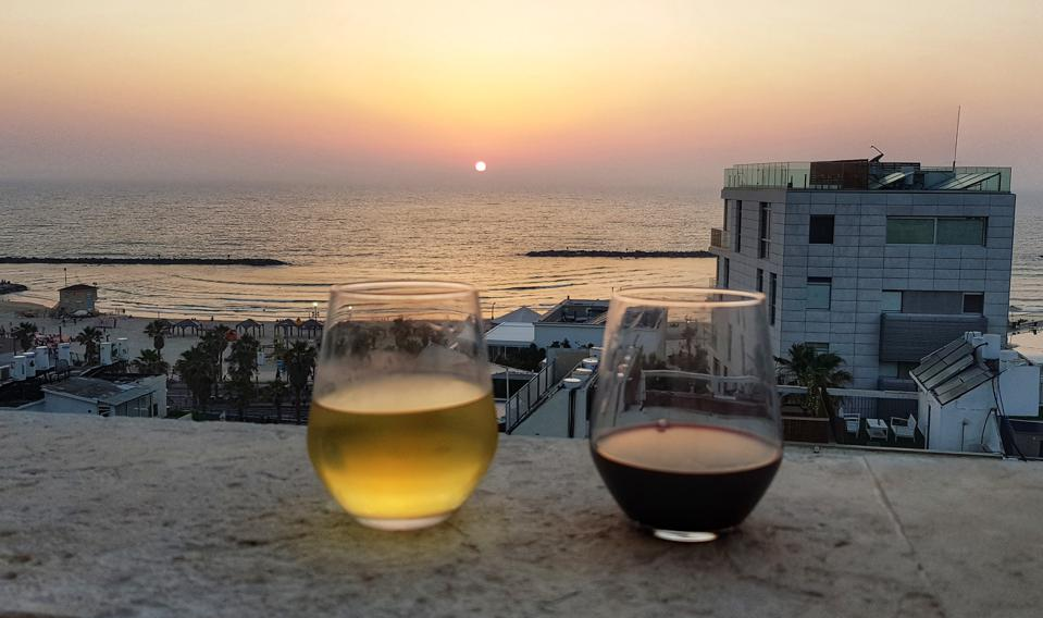 Two glasses of red and white wine on the rooftop in Tel Aviv, Israel and the setting sun at the beach.