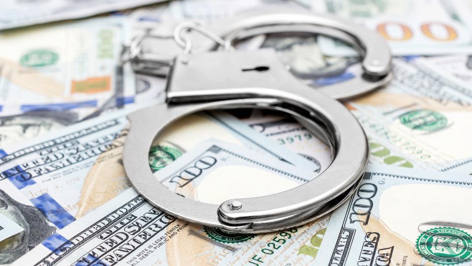 Handcuffs on the background of dollar bills.