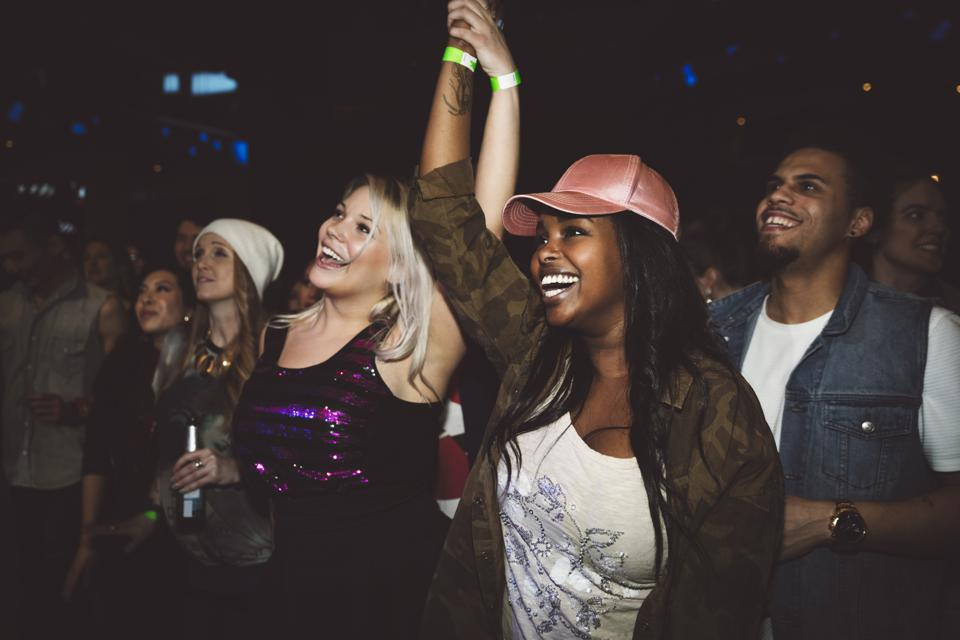 Happy, exuberant millennial women friends dancing at music concert in nightclub