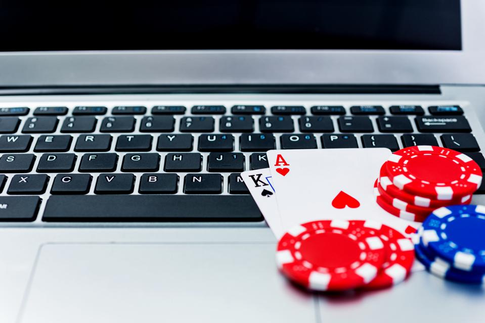 Poker chips and cards on computer keyboard