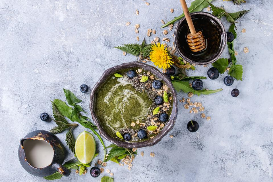 Spring green nettle and dandelion smoothie bowl served with lime, yellow flowers, young leaves, oat flakes, chia seeds, blueberries, cream and honey over gray blue texture background. Top view, space