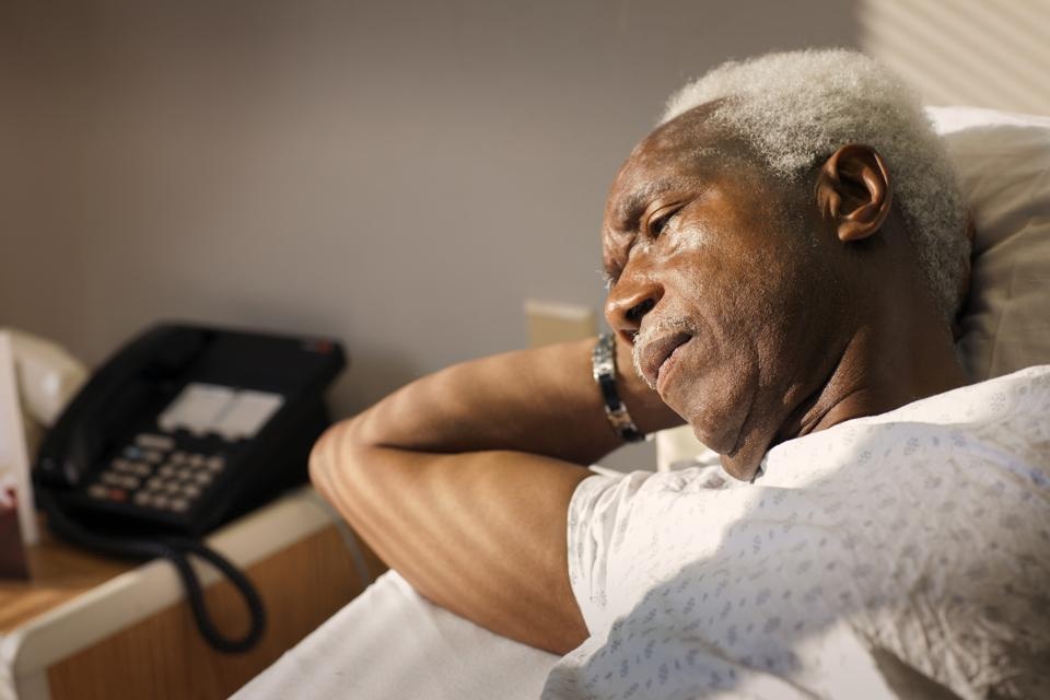 High angle view of thoughtful man lying on bed in hospital