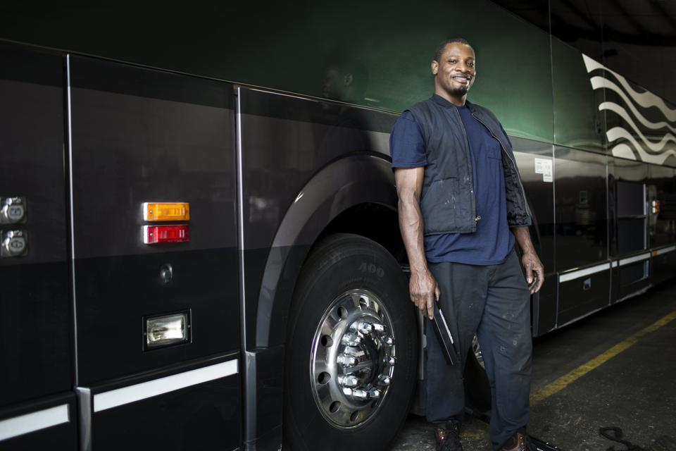 Portrait of mechanic standing by bus against sky