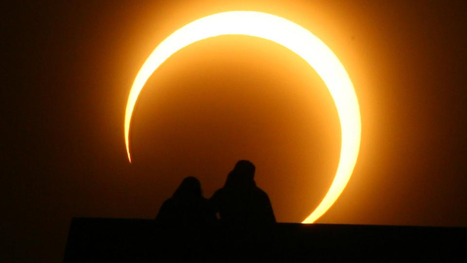 A Chinese couple watches an annular solar eclipse over Zhengzhou, China on January 15, 2010.