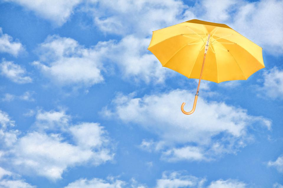 Mary Poppins Umbrella.Yellow umbrella flies in sky against of white clouds.