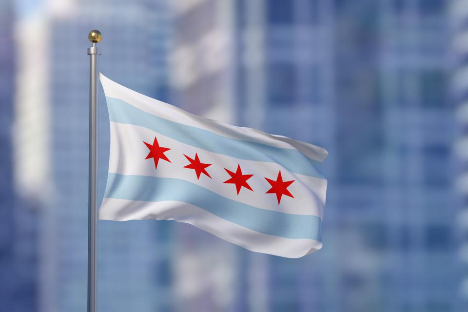 Chicago city flag blowing in the wind with buildings in background
