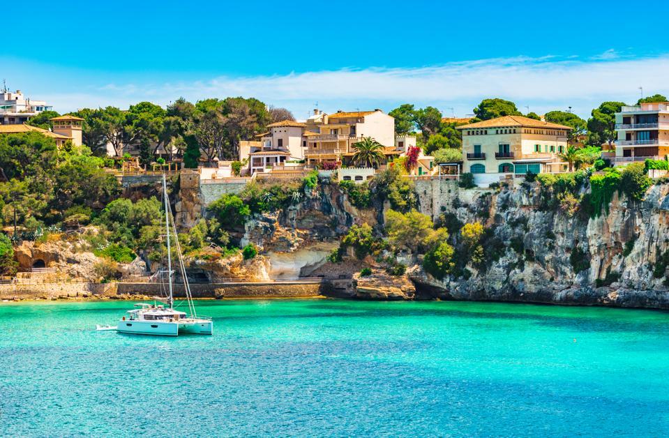 Mediterranean Sea Spain, idyllic bay with boat at the coast of Porto Cristo on Majorca island