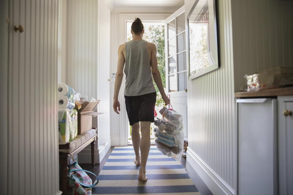 Rear view of man taking out garbage from home