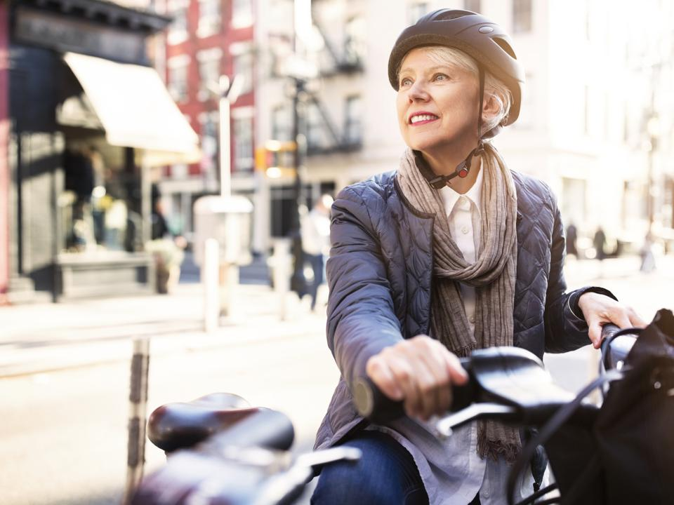 Thoughtful senior woman sitting on bicycle in a city
