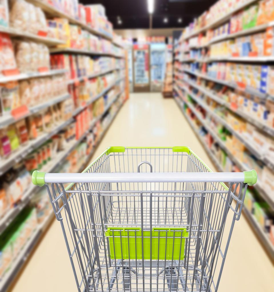 Supermarket aisle with empty shopping cart business concept