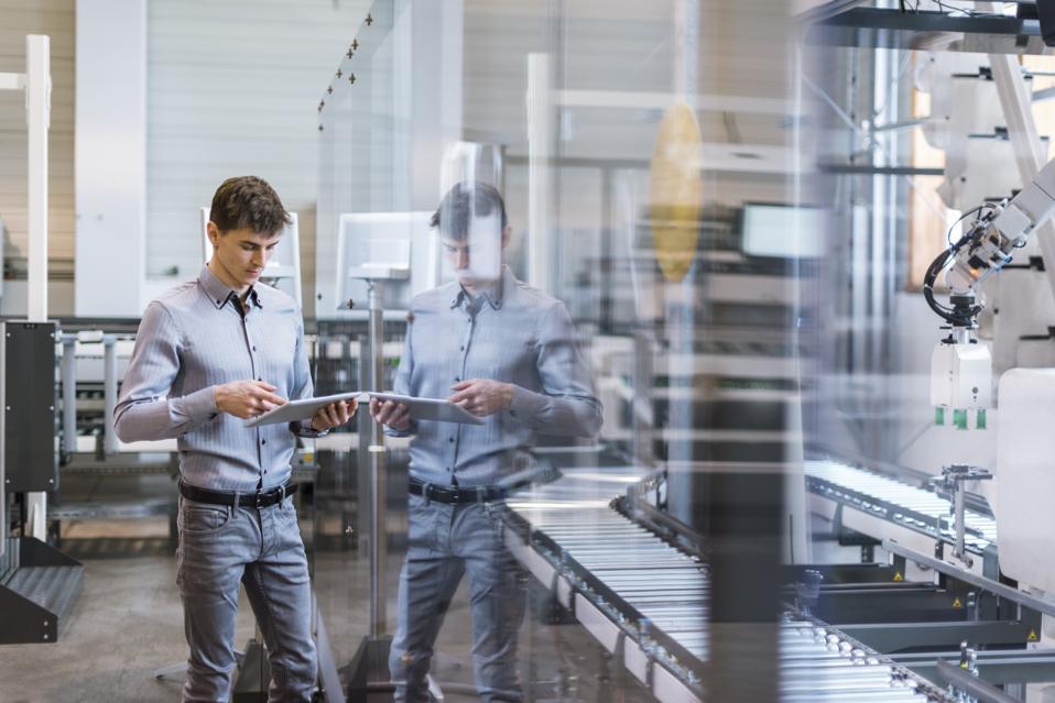 Младић у фабрици, поред покретне траке, користи дигитални таблет