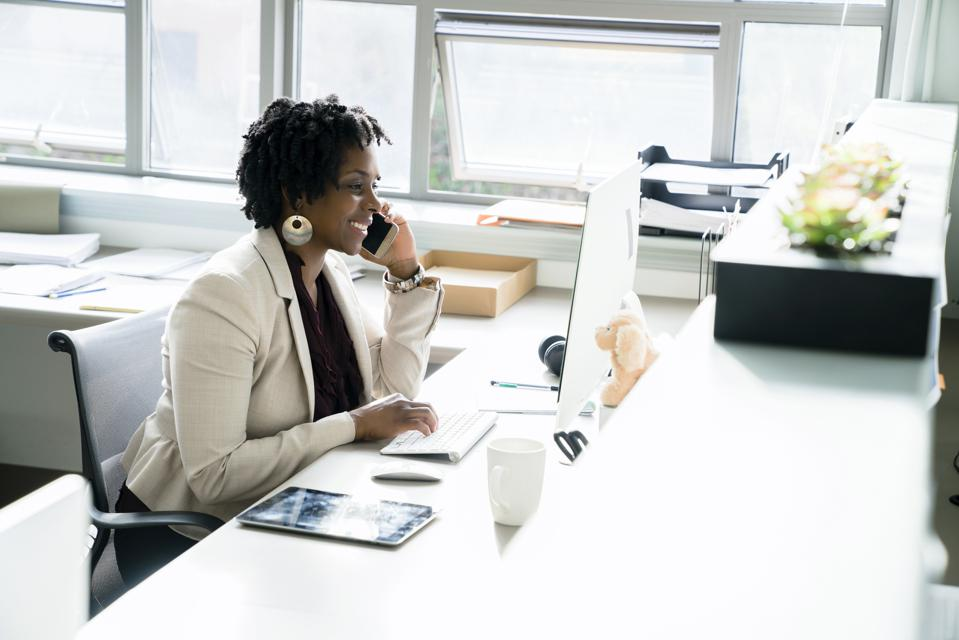 Businesswoman talking on smart phone while using desktop computer in office