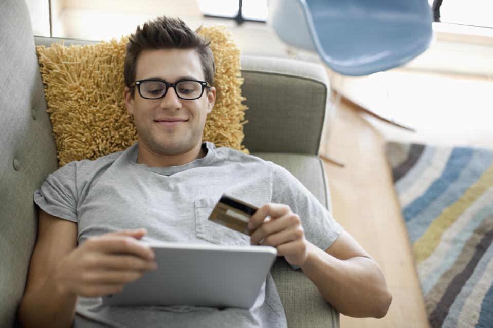Smiling man shopping online on tablet while lying on sofa at home