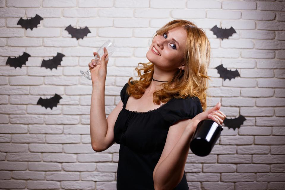 Happy gothic young woman with a bottle of wine and a glass. Hall