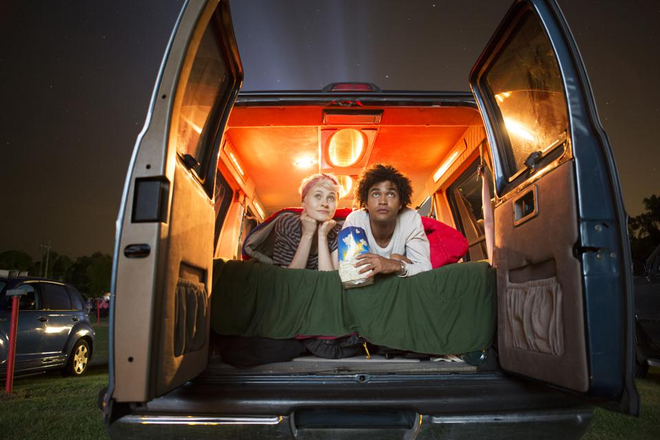 Couple holding popcorn while sitting in camping van during drive-in movie