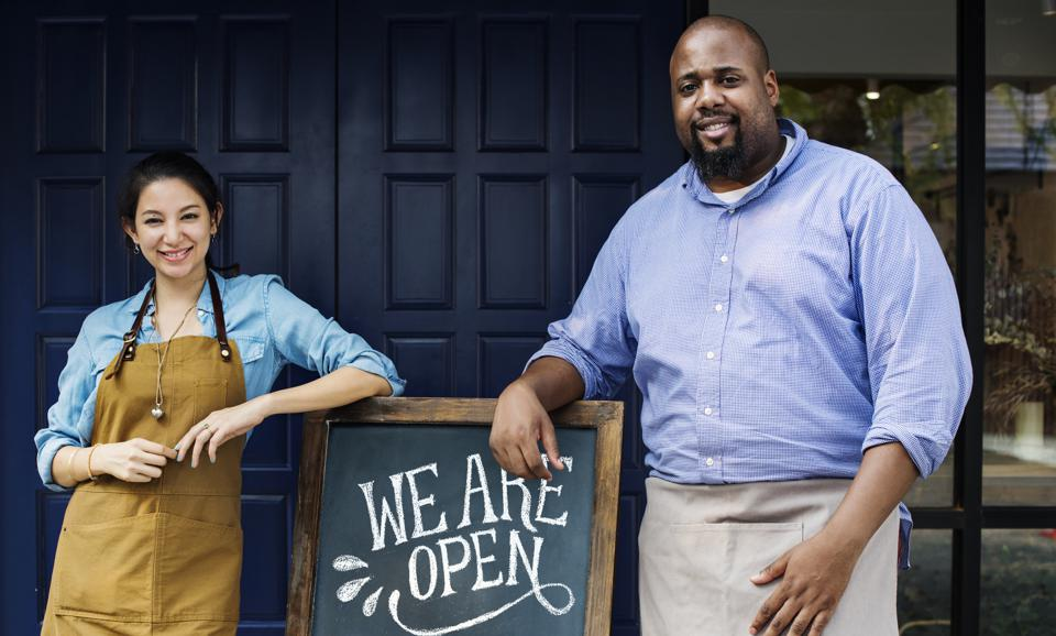 Cheerful business owners standing with open sign on blackboard