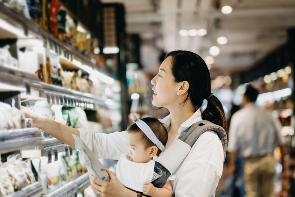 Beautiful Asian woman carrying baby girl shopping for products in grocery store