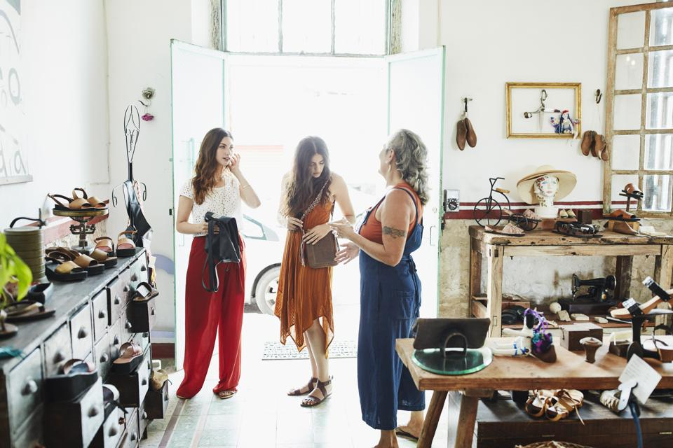 Shop owner helping two friends shopping in handmade leather goods store