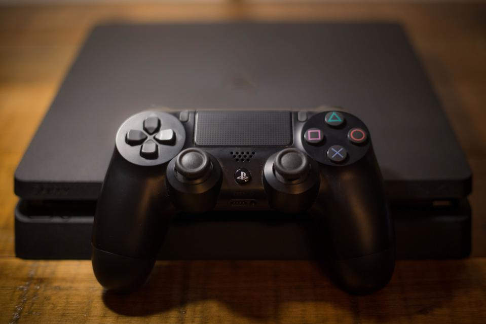 A Sony PlayStation 4 video game console with a black...
