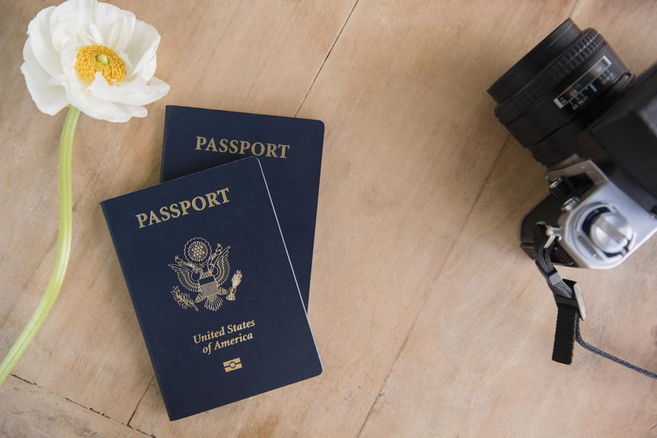 Passport, flowers and camera on table