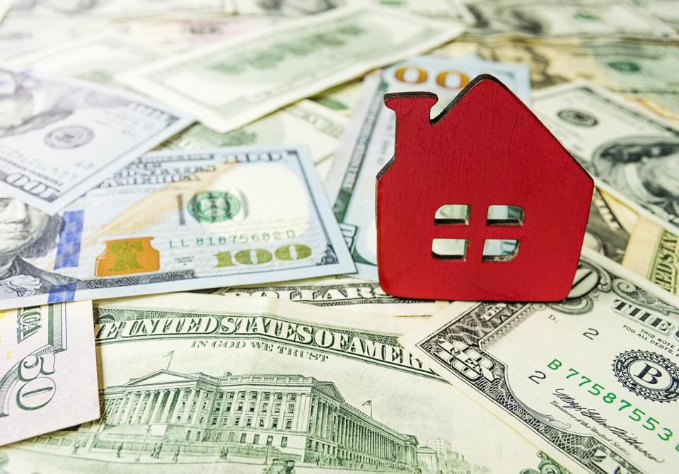Wooden model house on the background of U.S. dollar bills. Symbolic image of buying or renting a house. Selective focus, copy-space.