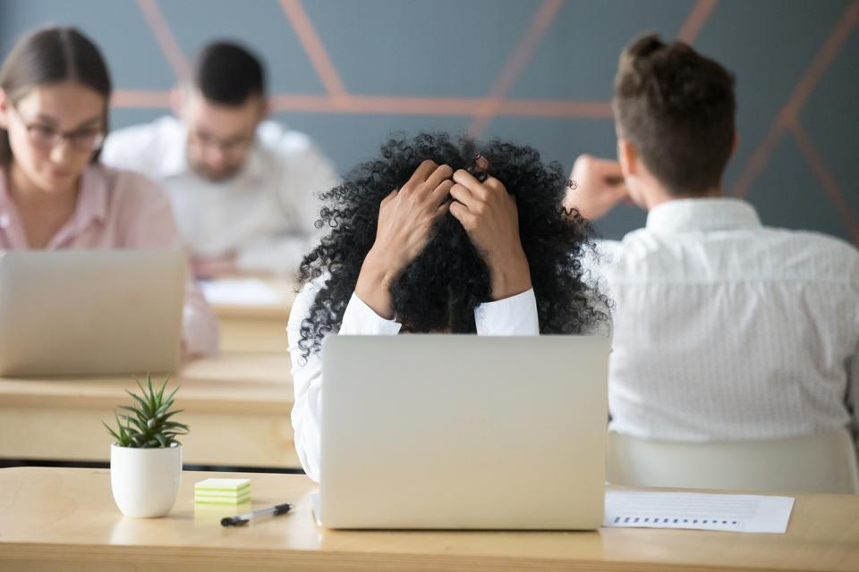 Frustrated african-american woman feeling despair in shared office with laptop