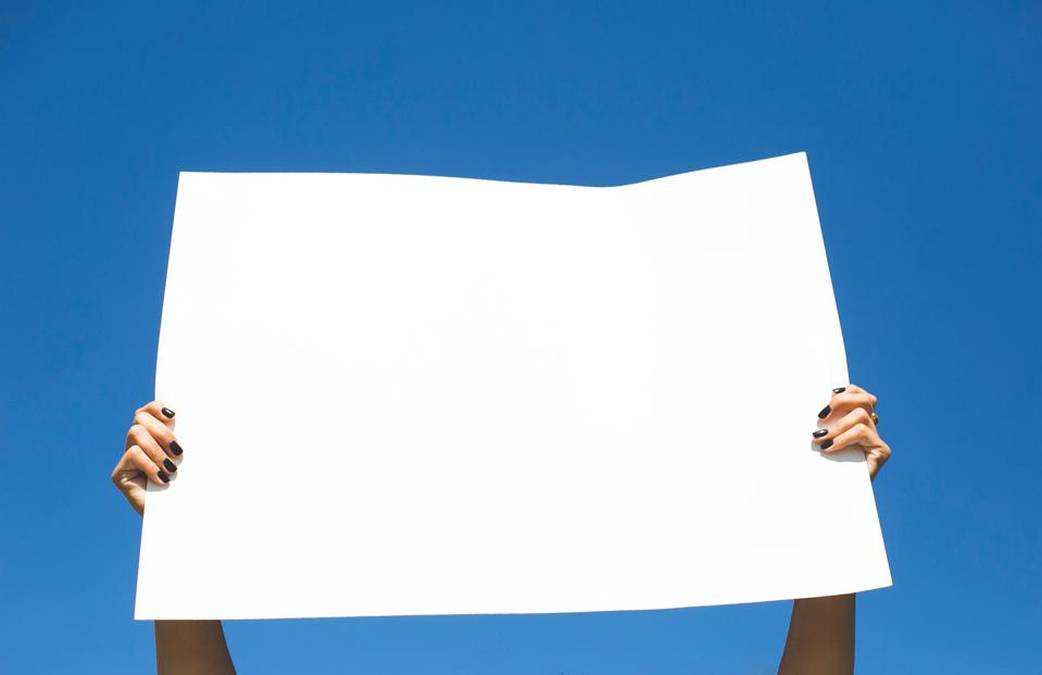 Low Angle View Of Woman Holding Placard Against Blue Sky