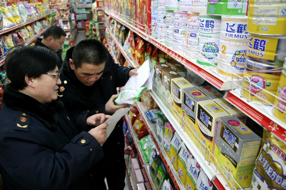 Three Chinese people in supermarket aisle, inspecting packages