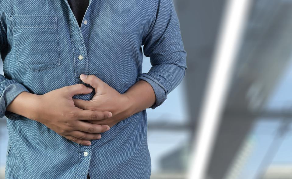 Midsection Of Man Touching Abdomen While Standing Against White Background