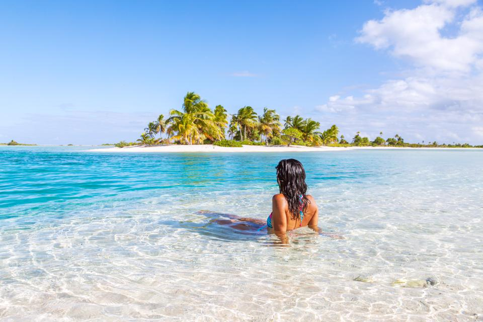 Woman sitting in a blue lagoon in front of tropical island