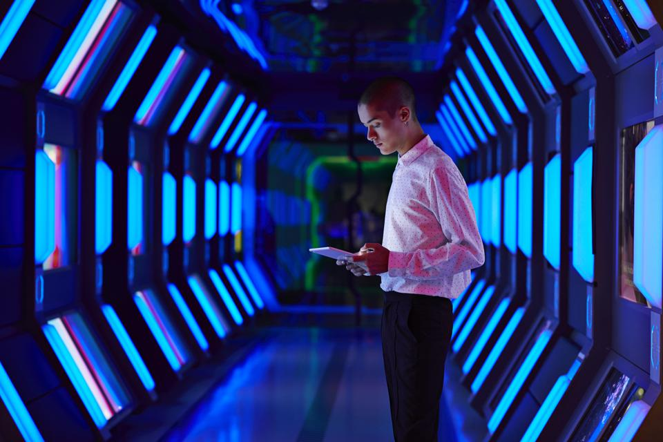 Young businessman looking at digital tablet in spaceship like corridor