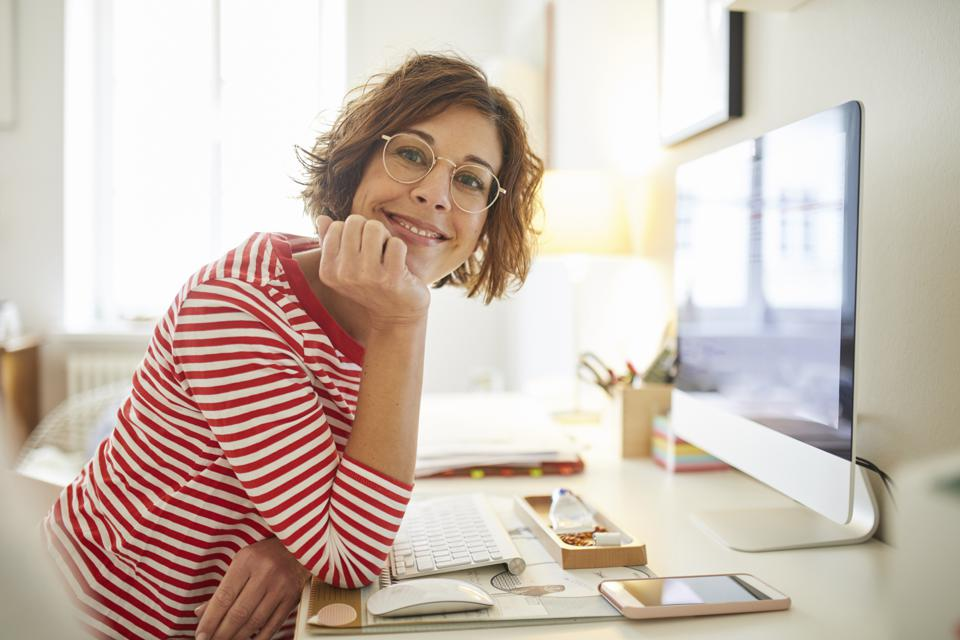 Portrait of content mature woman sitting at desk at home