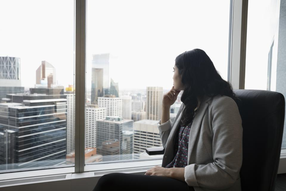 Forward looking businesswoman looking out urban office window