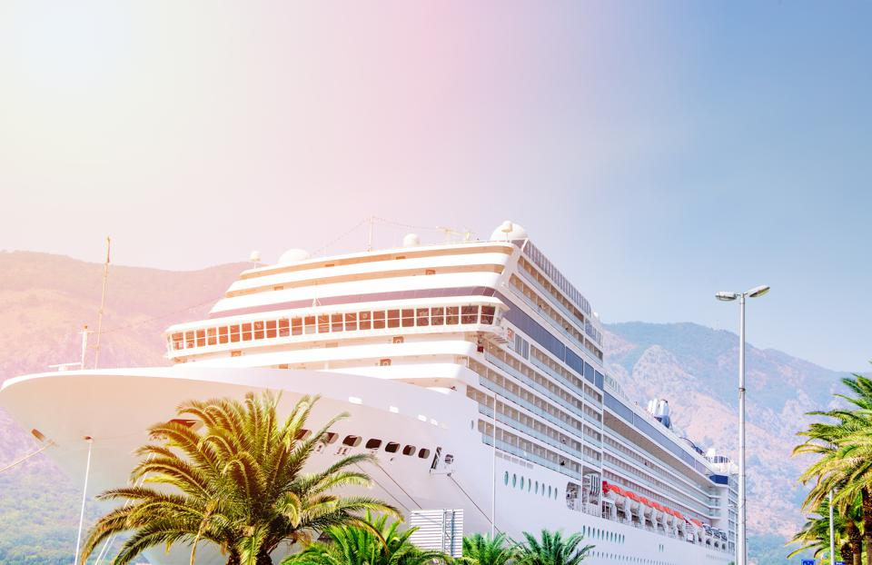 Cruise ship. Large luxury white cruise ship liner on sea water and cloudy sky background. Montenegro, Kotor