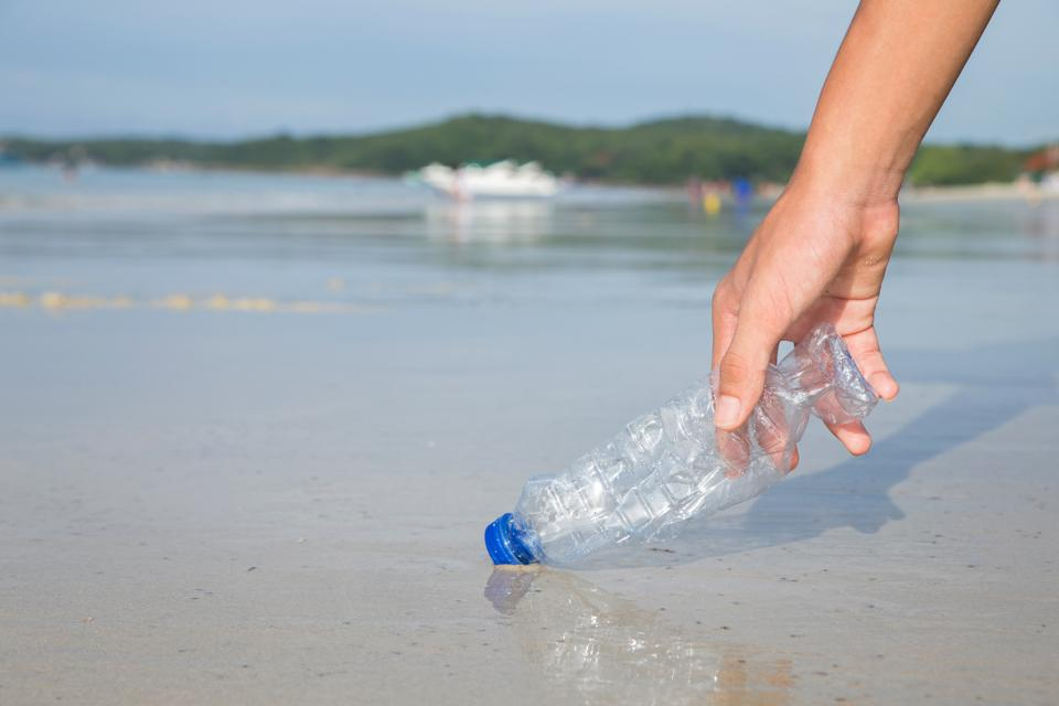 Hand picking up plastic bottle cleaning on the beach.″Campaign to clean.Save the world