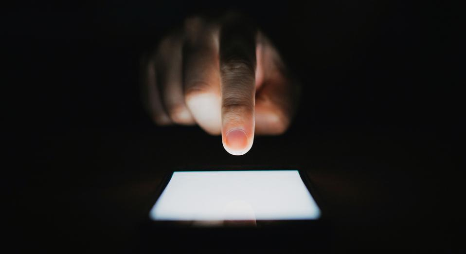 Close up of man's hand using smartphone in the dark