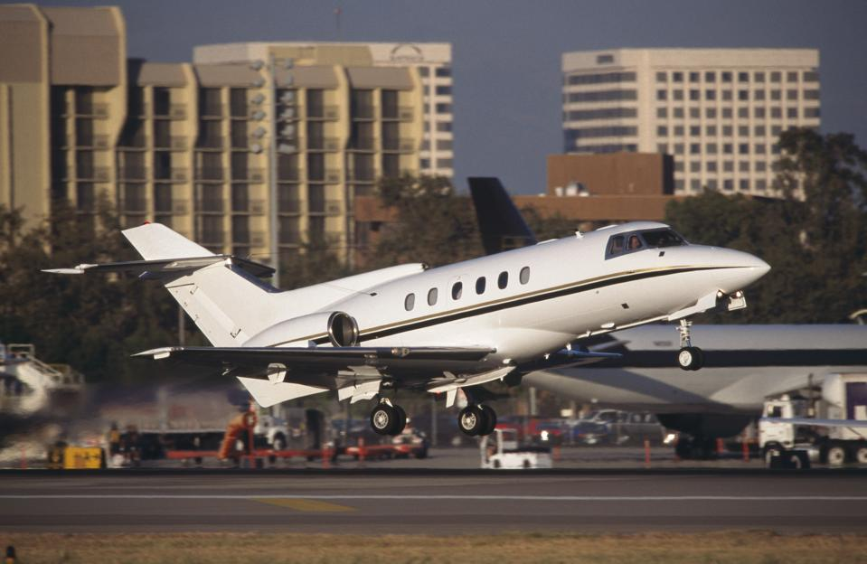 Hawker 800 business-jet taking-off with office-buildings behind