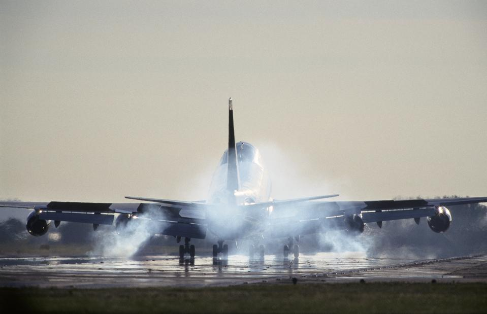 Boeing 747-400 with smoking tyres at touchdown landing on the runway
