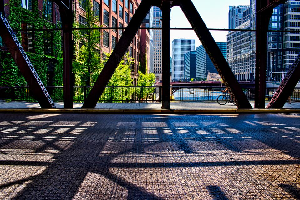 Bicyclist on Chicago's Lake Street underneath the shadows of the ″el″ bridge over Chicago River.