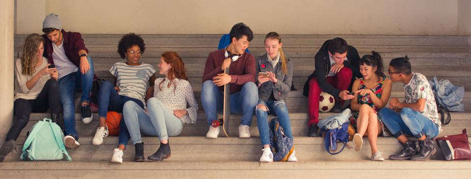Students chatting together and looking at smartphones between classes