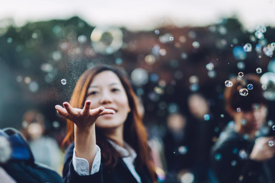 Young woman catching bubbles joyfully in park
