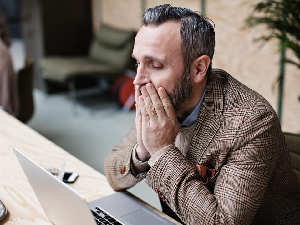 Tired businessman looking at laptop while sitting in office