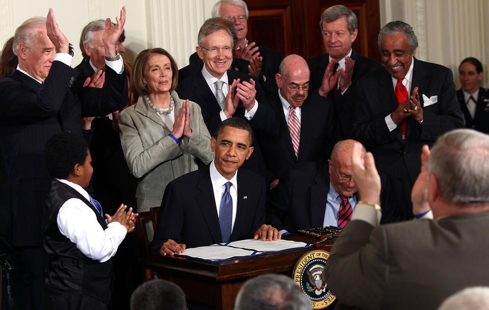President Obama Signs the Health Care Reform Bill surrounded by Democratic congressional leaders.